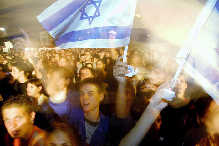 <em>Demonstrators sing peace songs during a rally in Tel Aviv in 2002.</em> Quique Kierszenbaum/Getty Images.