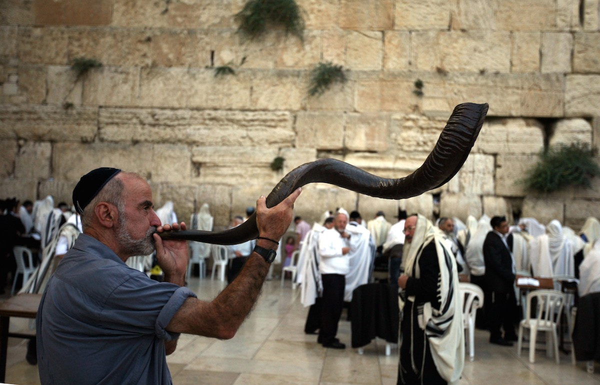 A man blows the shofar in Jerusalem for Rosh Hashanah. Photo by Awad Awada/Anadolu Agency/Getty Images.