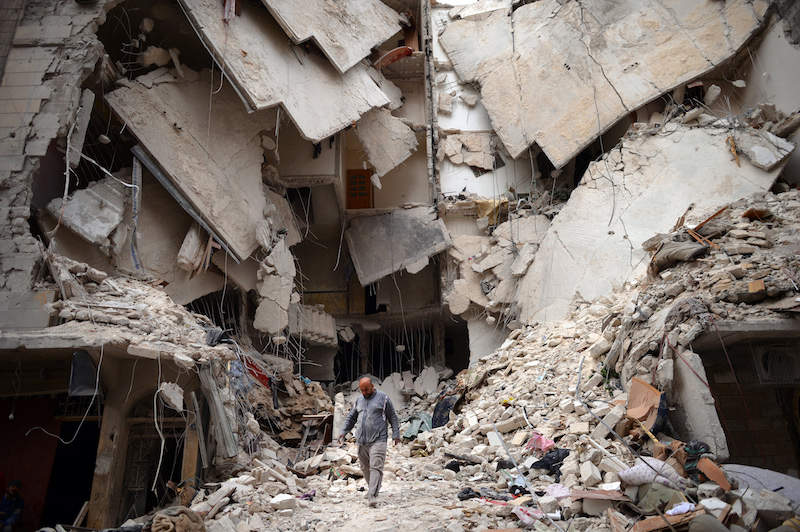 A Syrian man walks amid destruction in the northern Syrian city of Aleppo on April 10, 2013. © Dimitar Dilkoff/AFP/Getty Images.